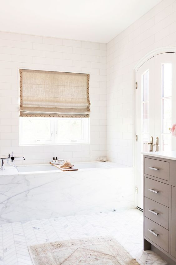 I can't get enough of the simple clean lines that structure the marble tub coupled with the chevron floors and the arched french doors.